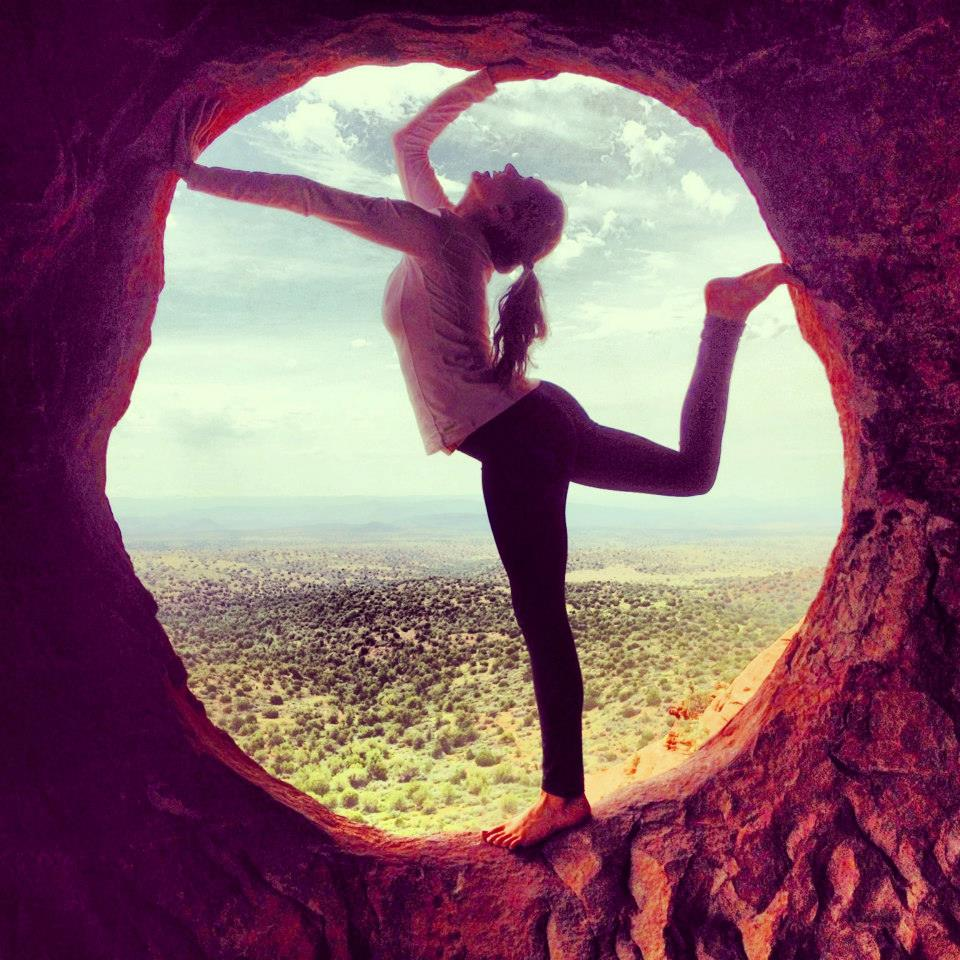 A beautiful picture of Bridget Nielsen posing in a circular red rock, Sedona Arizona
