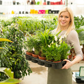 Smiling blond girl florist working in greenhouse demostrating The Value of each Individual Living their Passion