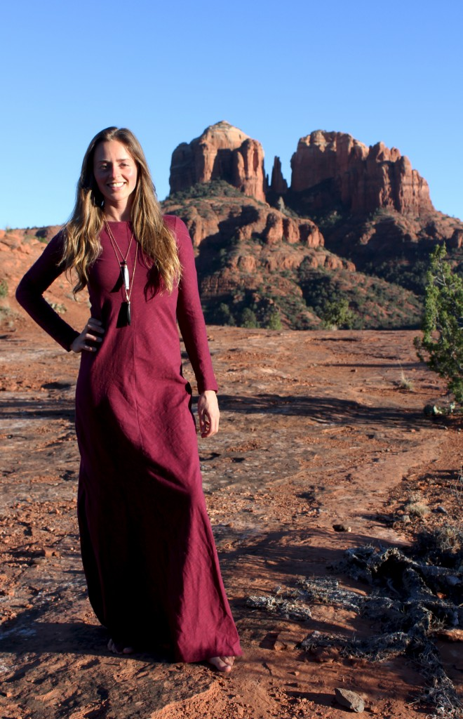 Girl in red dress in front of cathedral rock vortex in Sedona